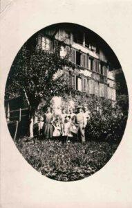 Bild: unbekannte Personengruppe in Garten vor einem Haus