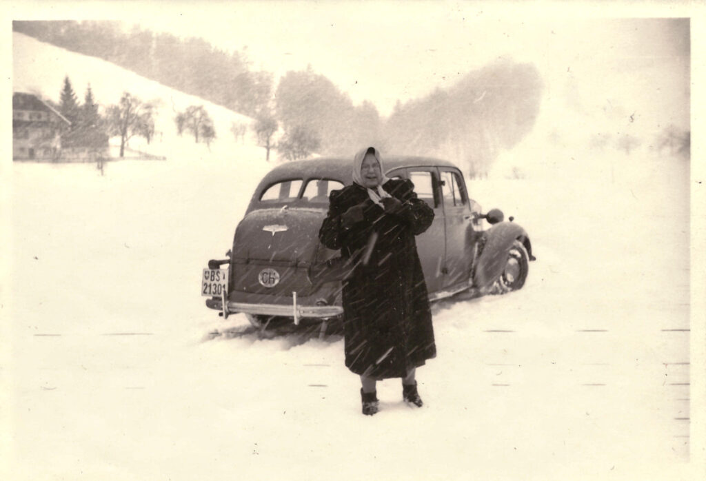 Maria Gürtler vor einer Limousine im Schneetreiben
