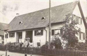 Bild: unbekannte Familie vor einem Einfamilienhaus, Ort und Jahr unbekannt