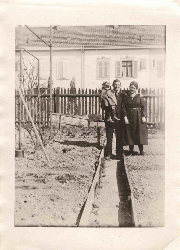 Anbauschlacht: unbekannte Familie im Vorgarten, Ort und Jahr unbekannt