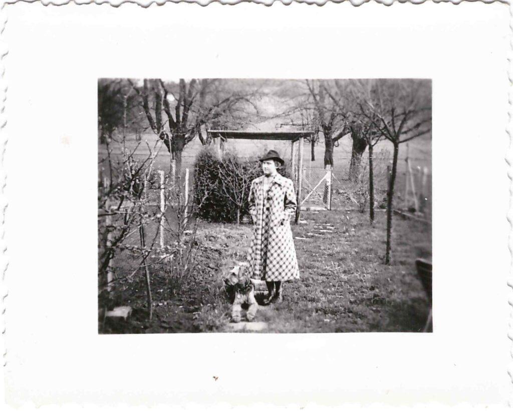 Mode: Gertrud Gürtler mit elegantem Mantel und Hut im Garten mit Hund Rex