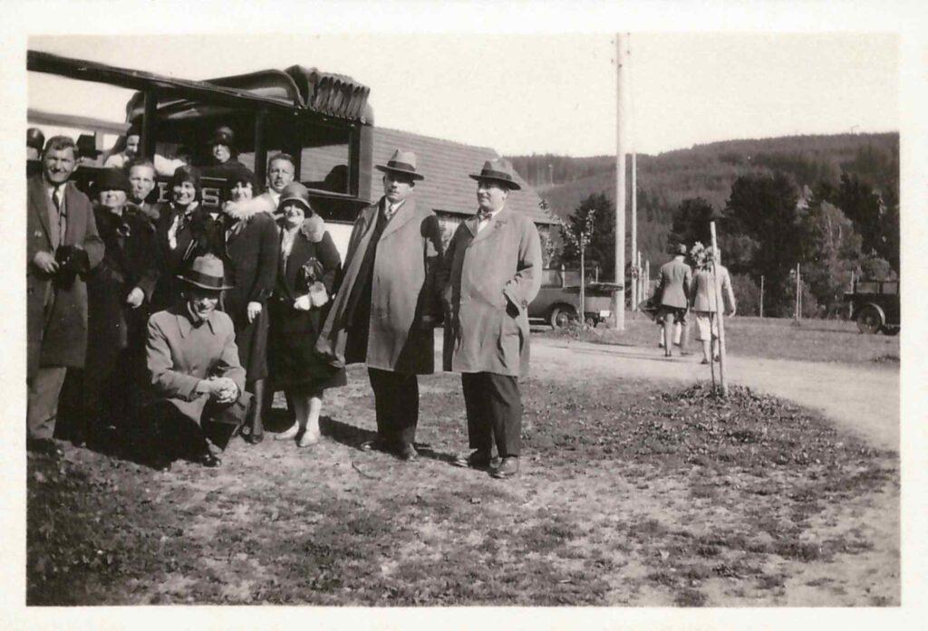Bild: Personengruppe vor Reisecar mit Hüten